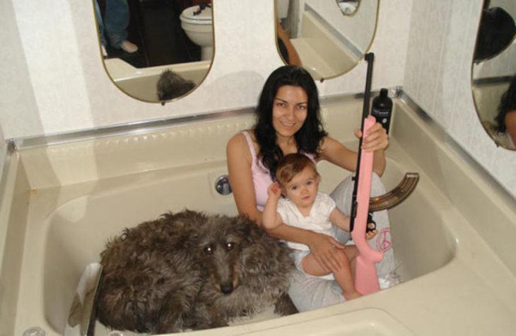 mujer en tina con bebé, arma y perro