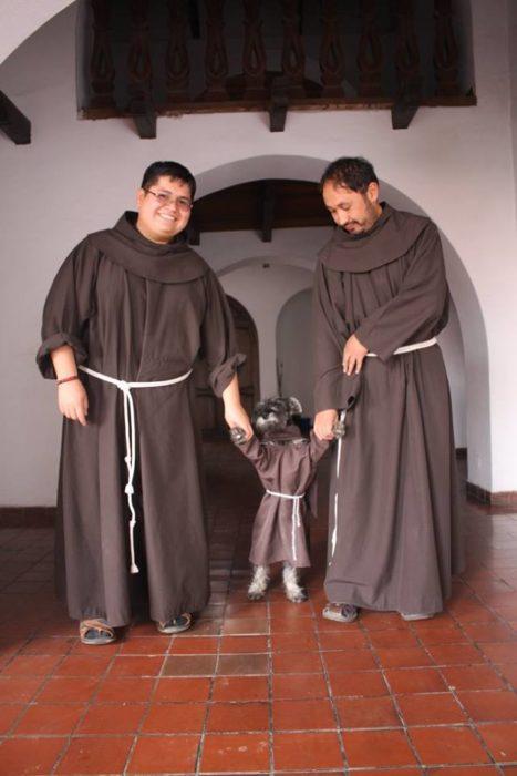 dos franciscanos tomando de las patitas a un perro con hábito