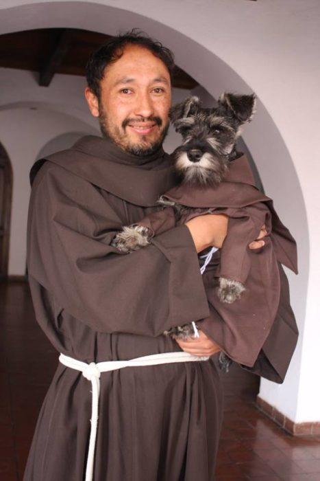 monje cargando a un perrito