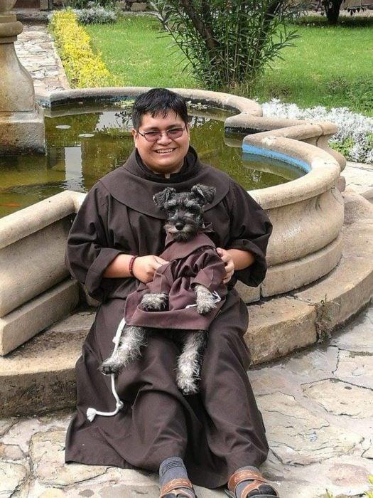 monje abrazando a perrito vestido con hábito delante de una fuente