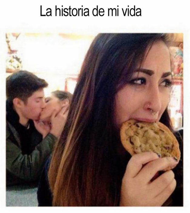 pareja besándose y adelante una chica comiendo una galleta