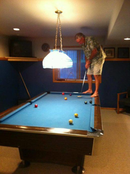 señor jugando golf en una mesa de billar