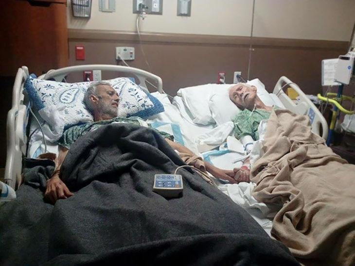 señores de edad tomados de la mano en camillas de hospital