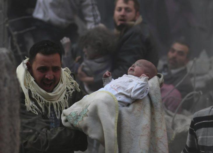 Hombre carga a bebé que sobrevivió a un ataque en Siria