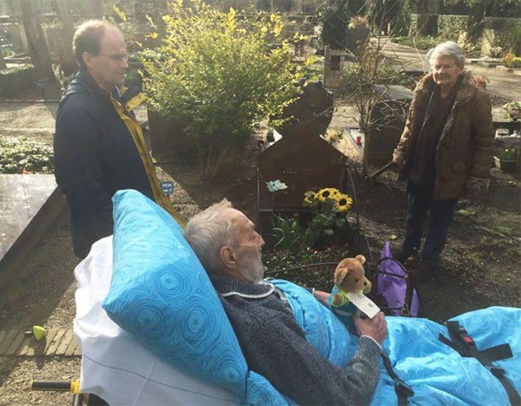 hombre en camilla de hospital carga un osito de peluche a una tumba