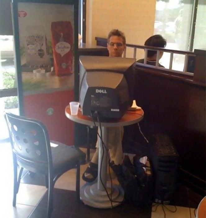 hombre con una pc de escritorio en un restaurante