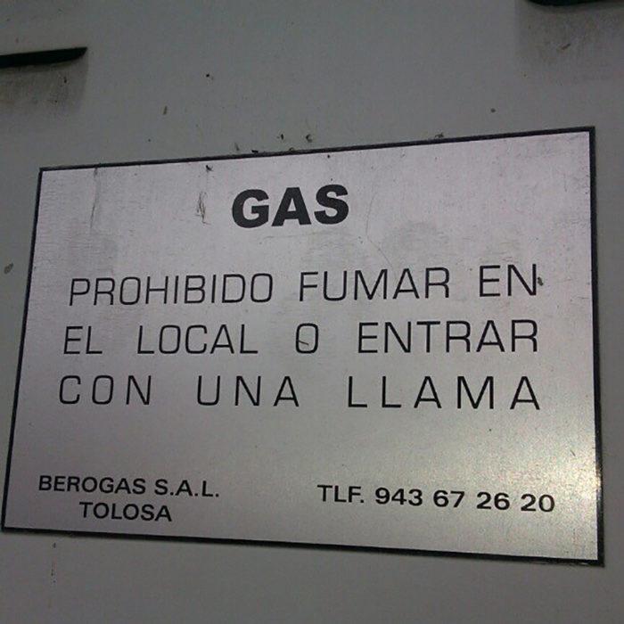 letrero que dice no fumar o entrar con una llama