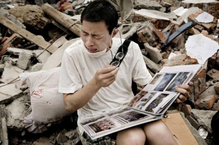 hombre llora mientras sostiene uun album de fotos en medio de los escombros