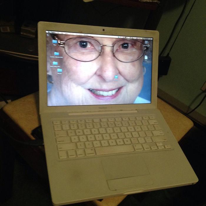 laptop con la foto de una anciana como fondo de pantalla