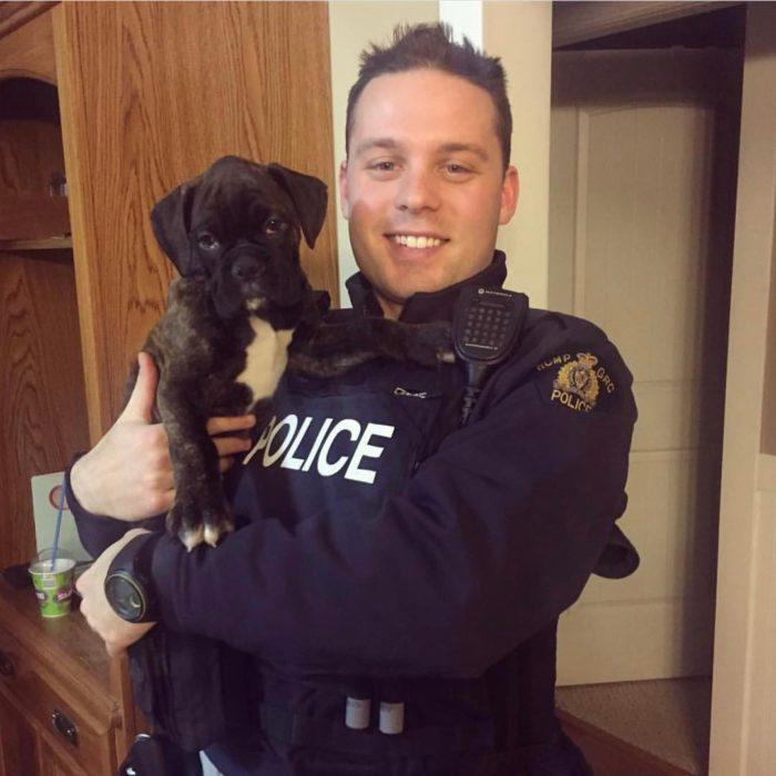 policía sonriendo y cargando un cachorro