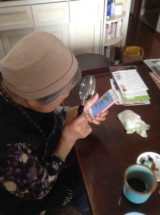 señora mirando el celular con una lupa