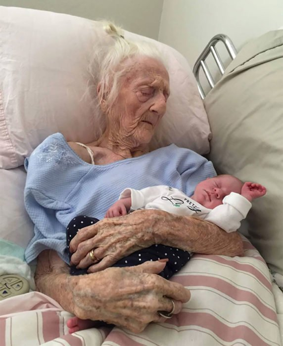 anciana en cama cargando a una bebé