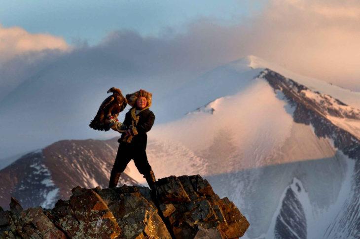niña en las montañas con un ave en su mano