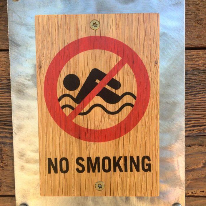 cartel que dice no fumar pero tiene el símbolo de no nadar