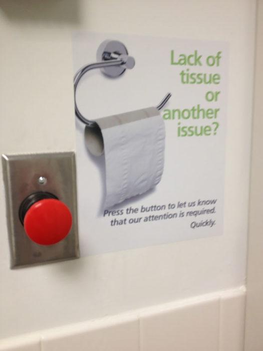 puerta de baño con botón rojo para presionar si te quedas sin papel