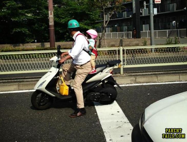 hombre en motocicleta con una niña en una mochila