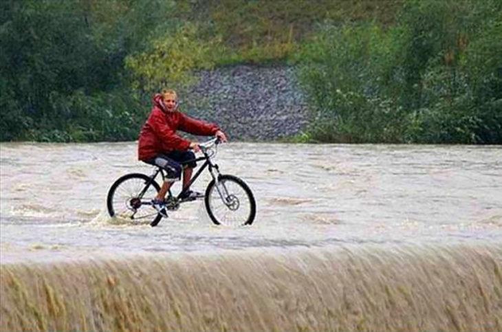 hombre manejando una bicicleta en una cascada