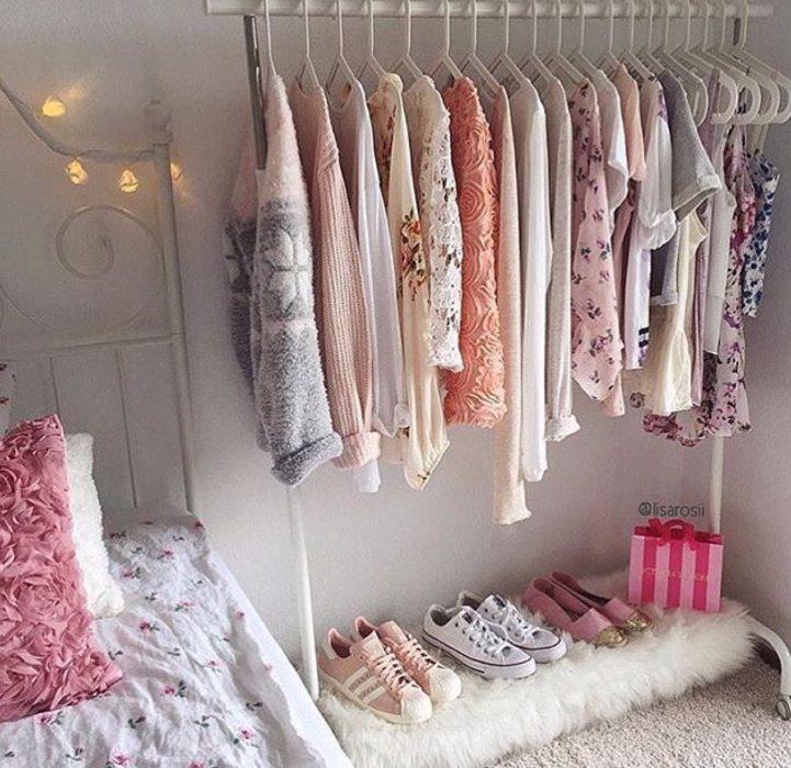 perchera con ropa en tonos rosados