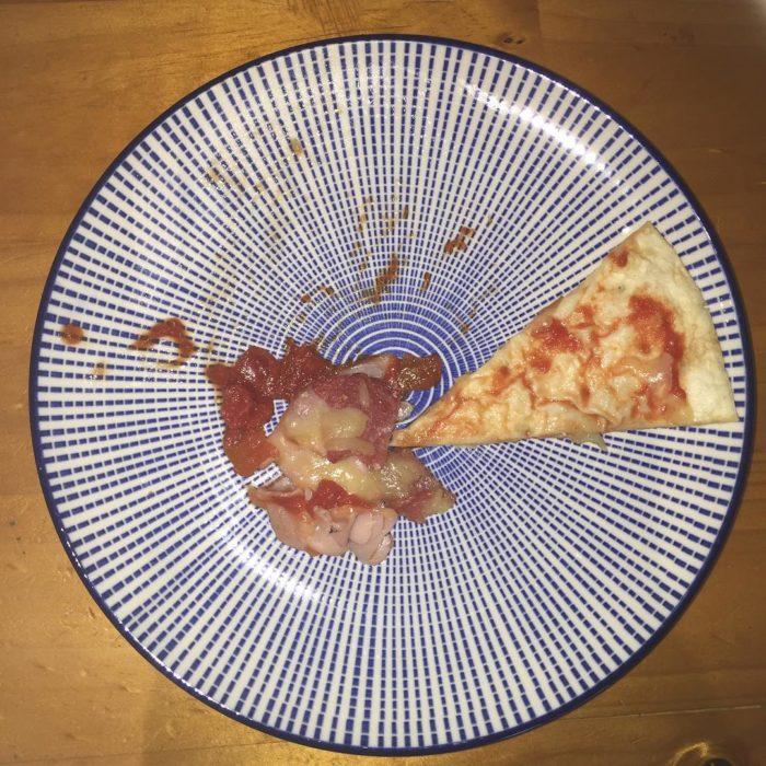 rebanada de pizza sobre un plato blanco con rayas azules