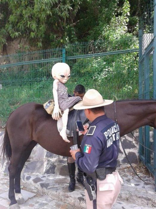 alien sobre un caballo y un policía