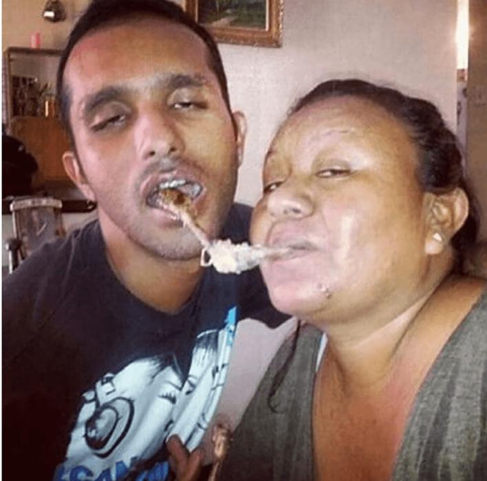 pareja compartiendo el pollo con la boca