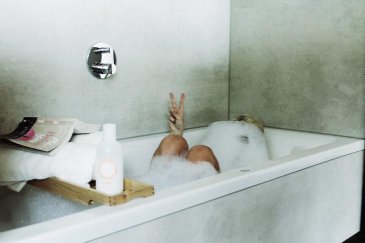 persona haciendo signo de amor y paz en la bañera