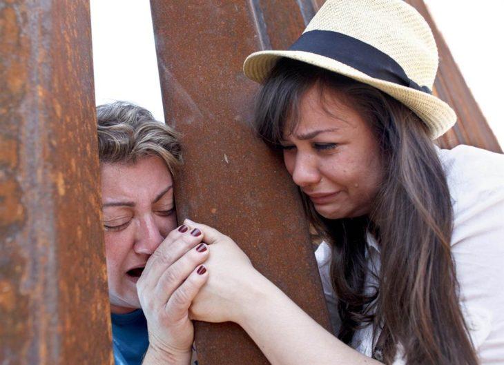 mujer sostiene la mano de su madre en la frontera