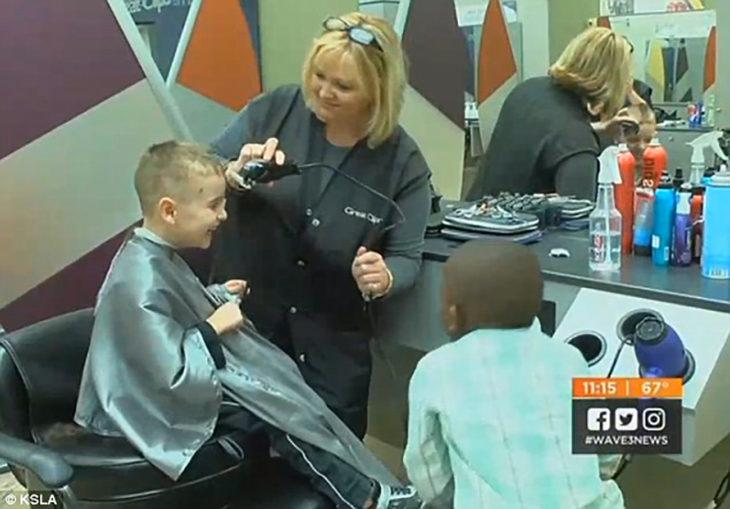 niño en una estética sentado en una sila mientras una mujer le corta el cabello