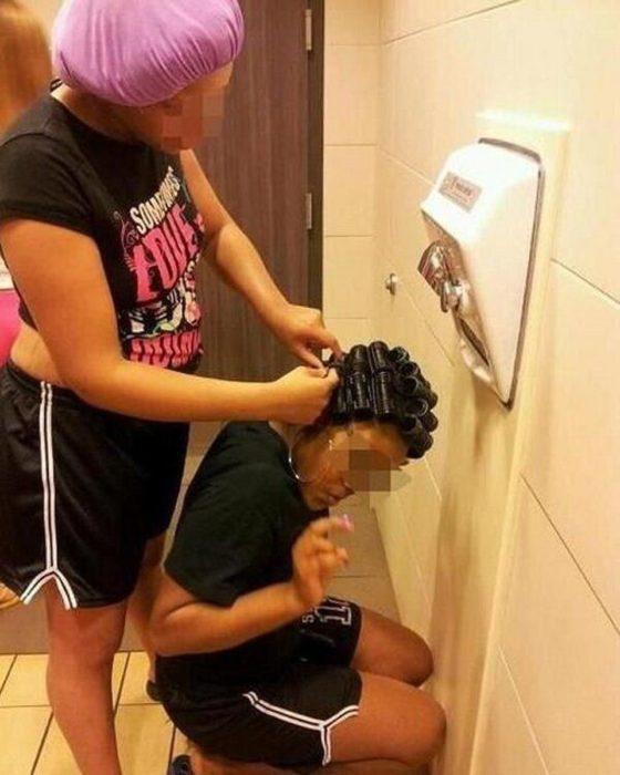 mujer secándose el pelo en el secador de manos de un baño