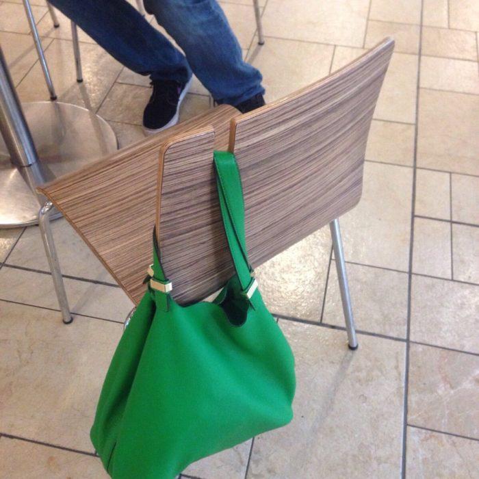 Silla con ranura para sostener bolsos con un bolso verde