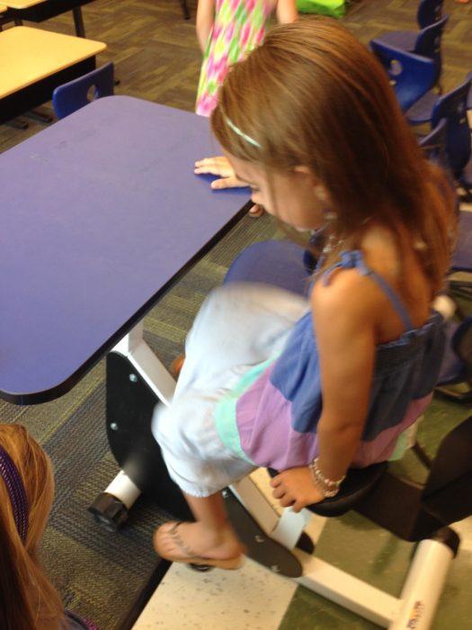 niña en una silla con pedales