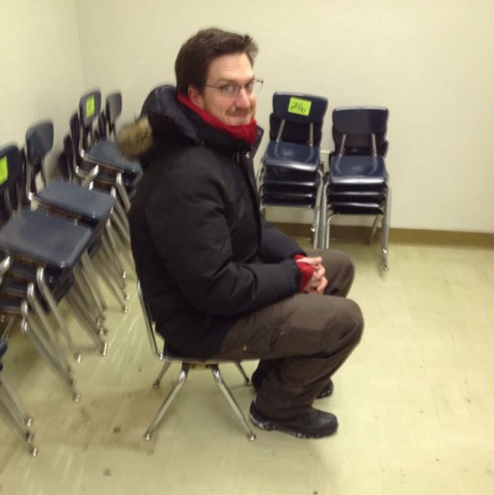 hombre sentado en silla pequeñita
