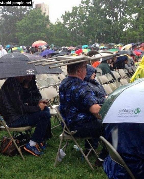 hombre utiliza una silla como paraguas