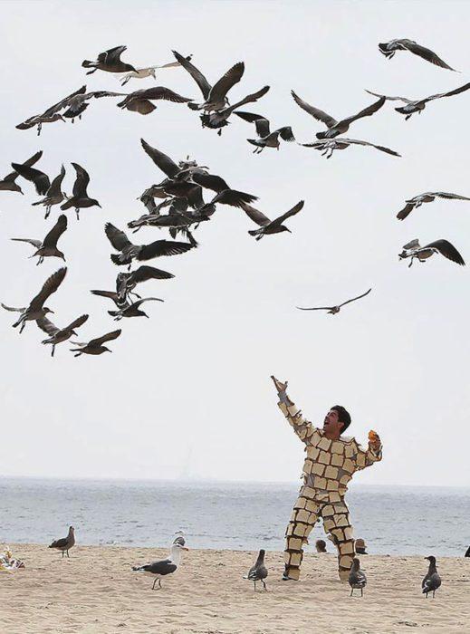 hombre con panes pegados al cuerpo y aves