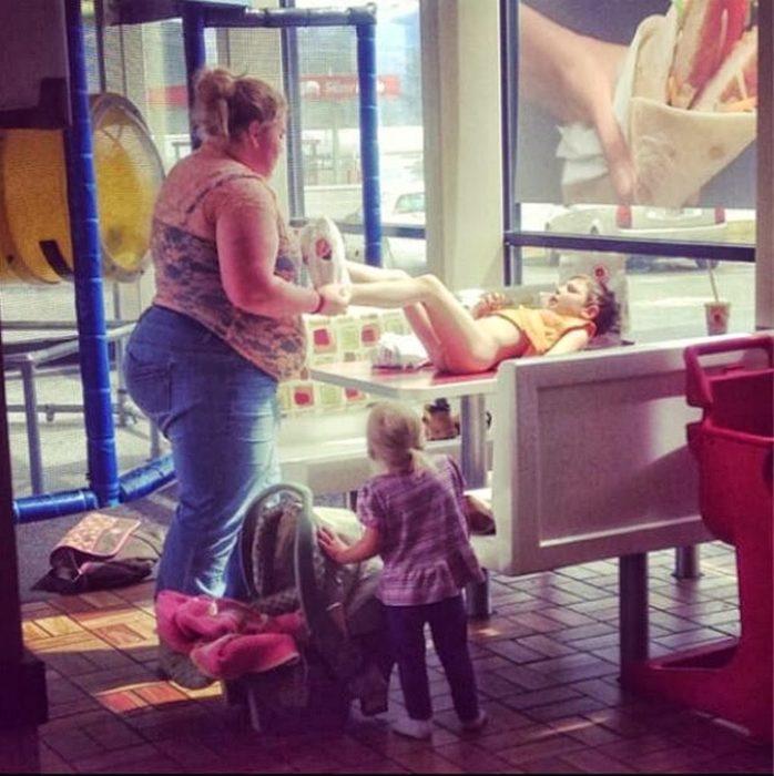 mujer cambiando pantalones a su hija sobre una mesa