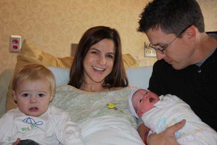 pareja en el hospital sosteniendo al recién nacido y al lado está el hijo que ya tenían