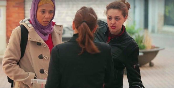 mujer con velo al lado de mujer con coleta y otra mujer en medio da la espalda a la cámara