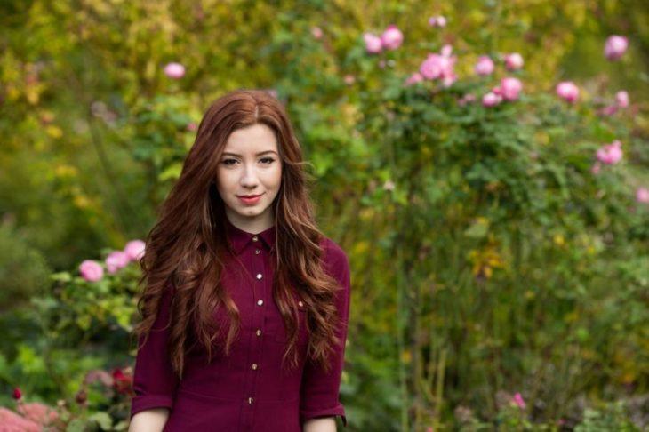mujer pelirroja en campo con flores