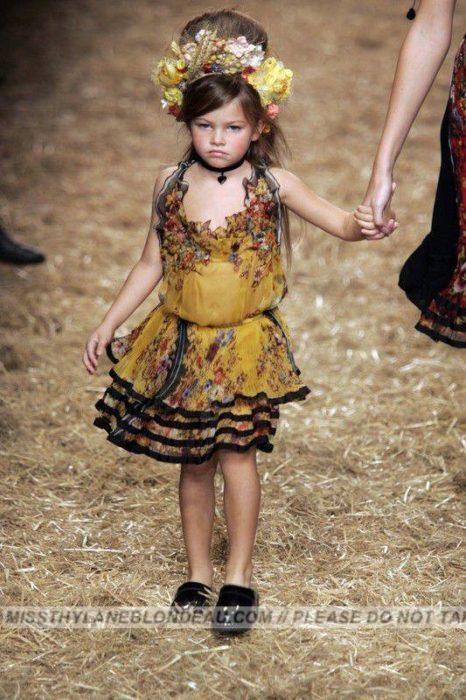 niña con corona de flores en una pasarela