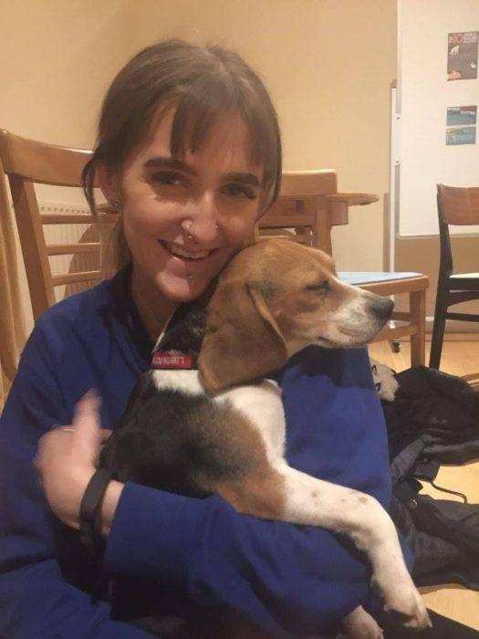 mujer abrazando a beagle mientras él duerme