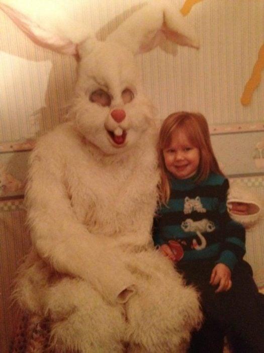 pequeña sonriendo junto al conejo de pascua terrorífico vintage