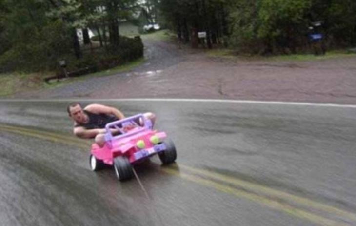 Hombre en carrito de juguete de niña jalado por un carro