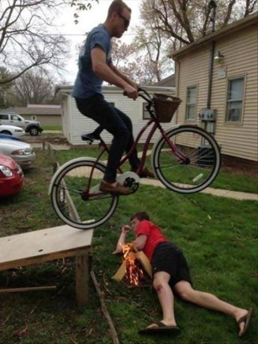 chico brincando en la bici sobre otro amigo