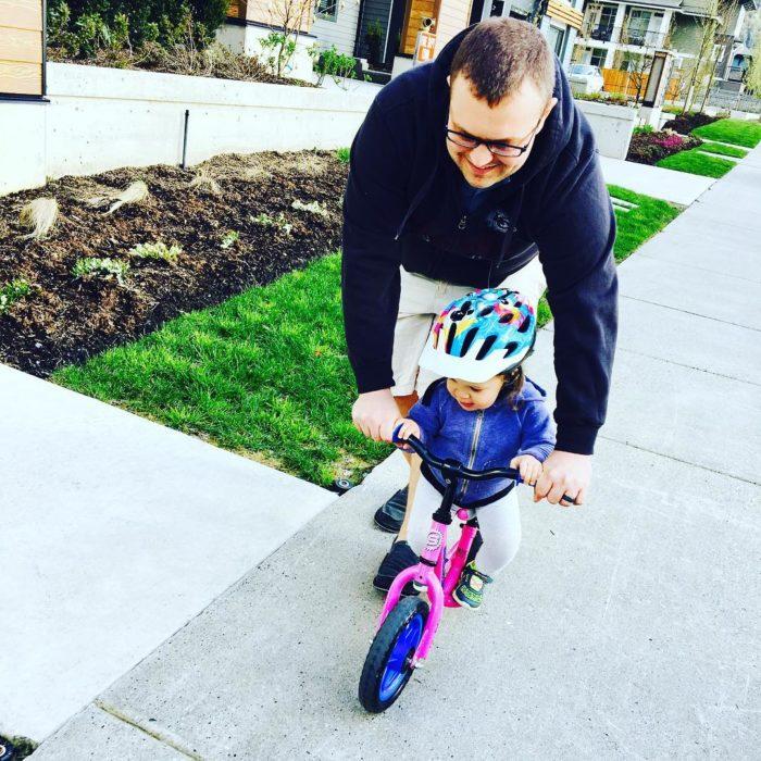 papá enseñando a su hija a andar en bici