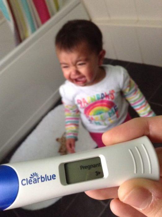 niño llora cuando su madre le muestra una prueba de embarazo