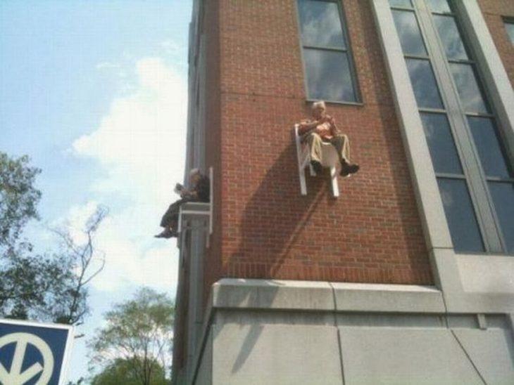 señor sentado en una silla pegada a muro de edificio