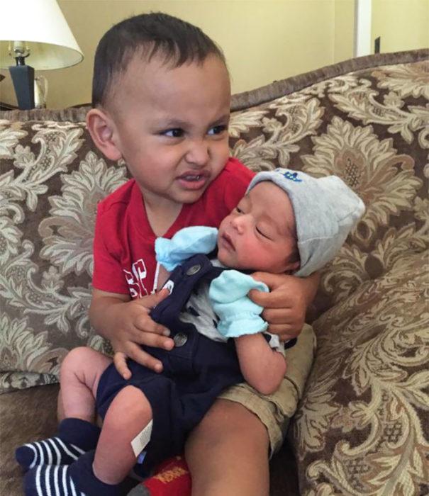 niño haciendo gesto gracioso mientras carga a su hermanito