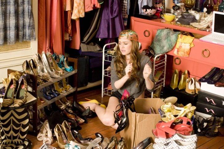chica sentada en el piso mientras observa su ropa