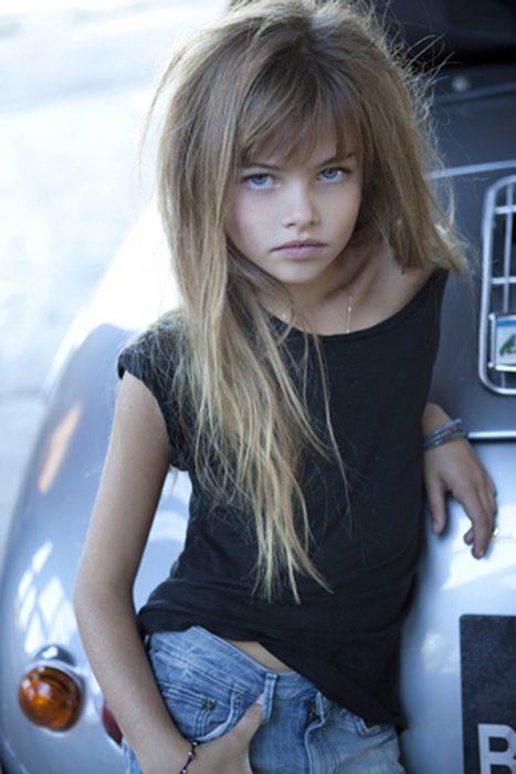 niña recargada en coche con el cabello despeinado