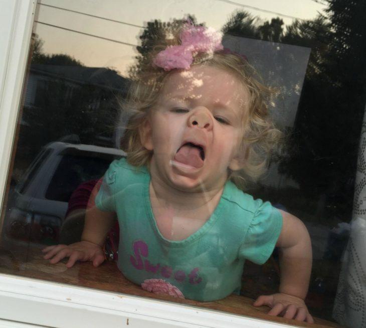 niña con el rostro pegado a un vidrio